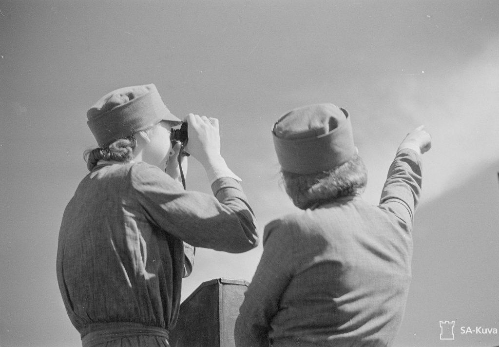 """Katolla, ilman suojaavia hiekkasäkkejä istuvat lotat suunnistaen vihollisten lentäjien lentoreittejä """" Tuolla se tulee"""" SA-kuva."""